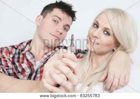 Close-up of a young couple receiving their new car's key sitting