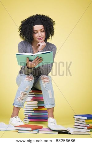 Smiling focused student girl reading while sitting on a stack of colorful books, isolated on yellow background.