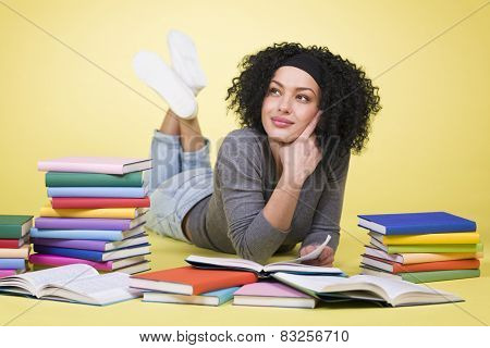 Friendly smiling student girl lying down on the floor while learning surrounded by multicolored books, isolated on yellow background.