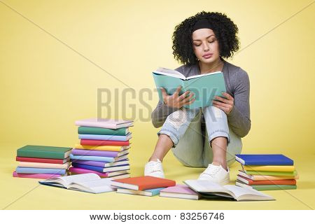 Serious student girl sitting on the floor and reading surrounded by colorful books, isolated on yellow background.