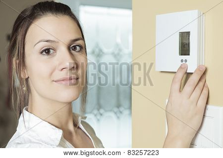 A woman set the thermostat at house.