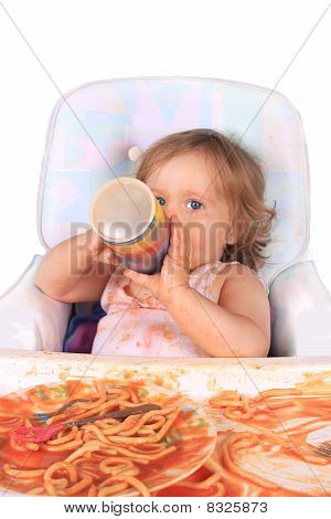 Messy Baby Girl Drinking Juice And Eating Spaghetti
