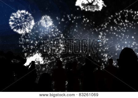 Silhouette of cheering people against white fireworks exploding on black background