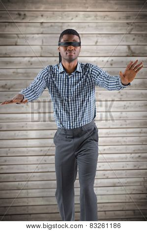 Blindfolded businessman with arms out against wooden planks background