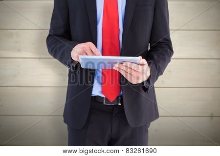 Businessman scrolling on his digital tablet against bleached wooden planks background