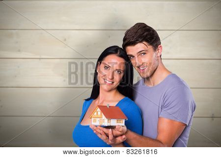 Young couple holding a model house against bleached wooden planks background