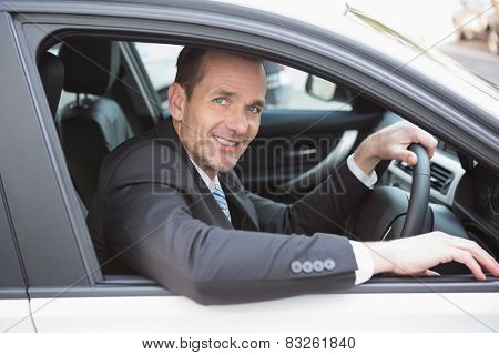 Happy businessman in the drivers seat in his car