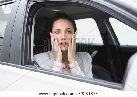 Nervous businesswoman looking at camera in her car