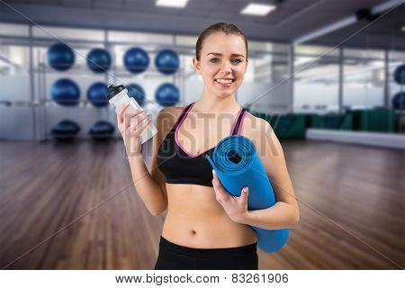 Fit brunette holding mat and sports bottle against large empty fitness studio with shelf of exercise balls