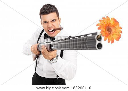 Angry guy shooting flowers from a rifle isolated on white background