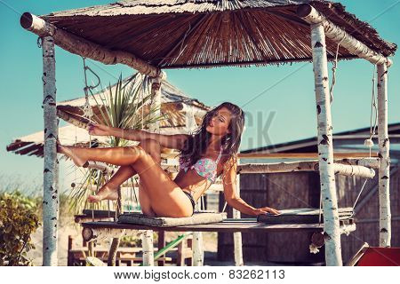 young woman in bikini  sit at shade at seaside beach enjoy in summer hot sunny day, full body shot