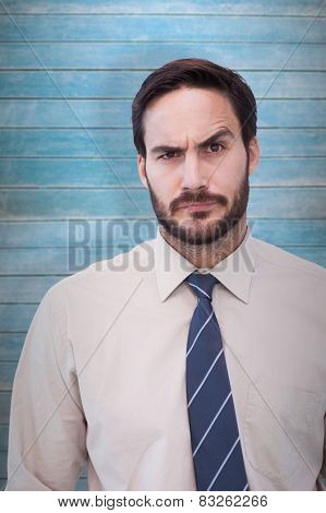 Portrait of a doubtful young businessman against wooden planks
