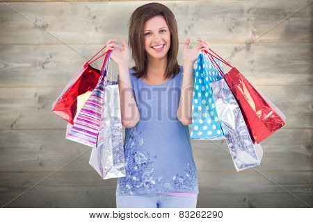 Portrait of cute young woman with shopping bags against bleached wooden planks background