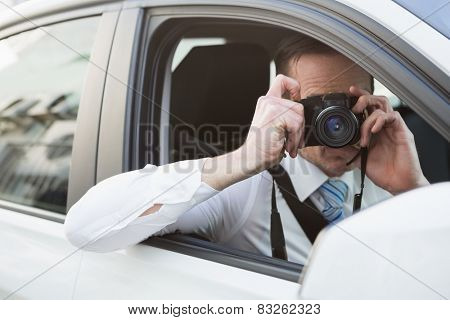 Businessman taking picture while sitting in the drivers seat in his car