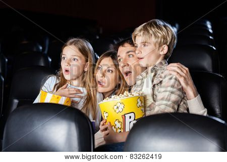Shocked family of four with popcorn watching movie in cinema theater