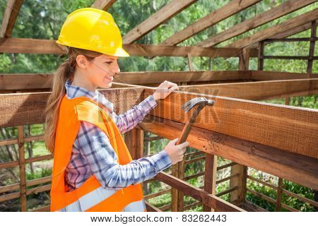 Side view of smiling female construction worker hammering nail on timber frame at site