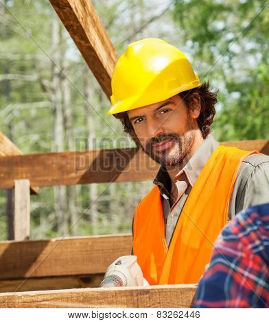 Portrait of confident male worker drilling on timber frame at construction site