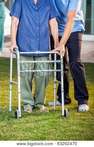 Low section of male caretaker helping senior woman in using walking frame at nursing home lawn