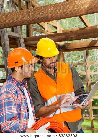 Male architects using laptop together in incomplete wooden cabin at construction site