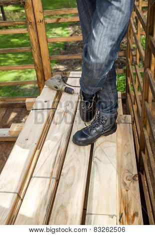 Low section of male construction worker standing by drill on stacked wooden planks at site