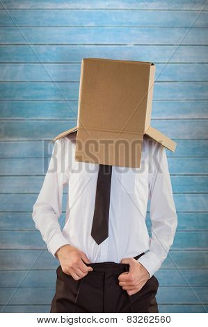 Anonymous businessman with hands in waistband against wooden planks