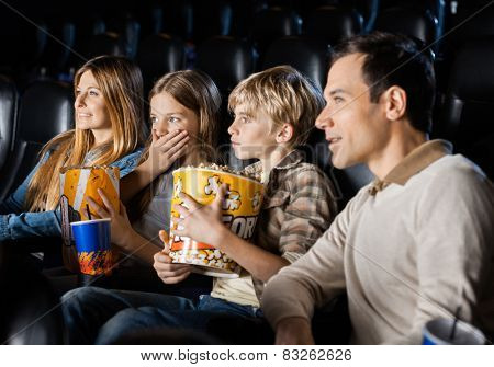 Family having snacks while watching movie in theater