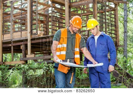 Male architects analyzing blueprint outside incomplete wooden cabin at construction site