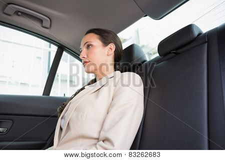 Unsmiling businesswoman sitting in the back seat in her car