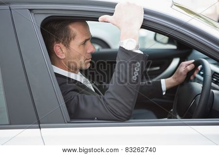 Focused businessman in the drivers seat in his car