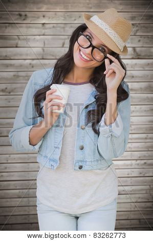 Brunette with disposable cup against wooden planks background