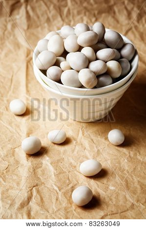 White Candies Like Sea Pebbles On Craft Paper
