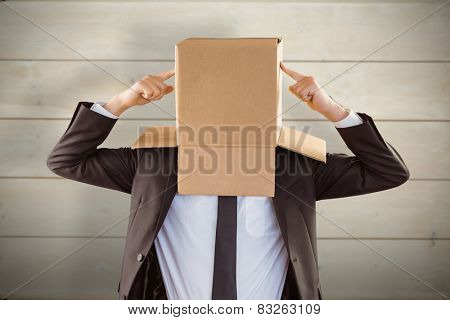 Anonymous businessman pointing to box against bleached wooden planks background