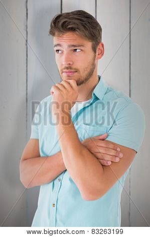 Handsome young man thinking with hand on chin against painted blue wooden planks