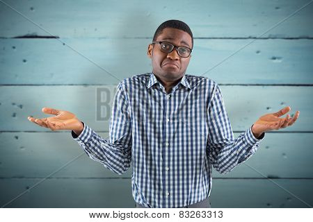 Young businessman shrugging shoulders against painted blue wooden planks