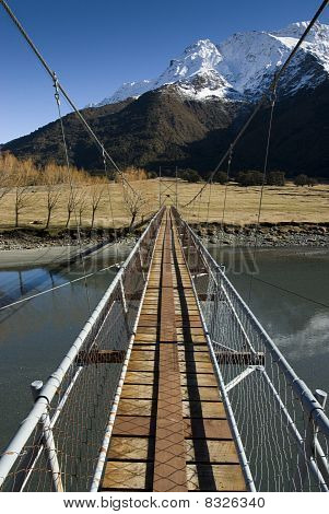 Swing Bridge crossing to snow capped Mountains