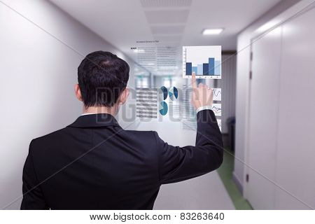 Asian businessman pointing against college hallway