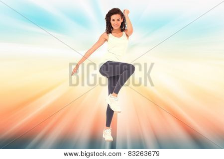 Fit woman doing aerobic exercise against abstract background