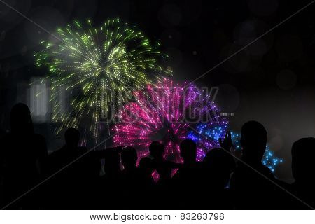 Silhouette of cheering people against colourful fireworks exploding on black background