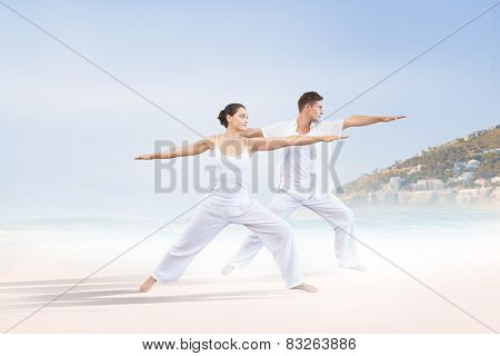 Peaceful couple in white doing yoga together in warrior position against beautiful beach and blue sky