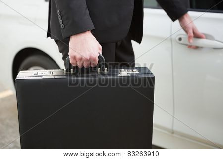 Close up of businessman holding a car door handles in a car park
