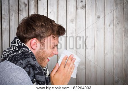 Close up side view of man blowing nose against wooden planks