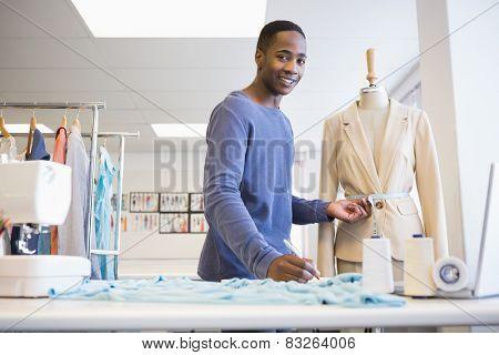 Smiling university student measuring waist of model at the university