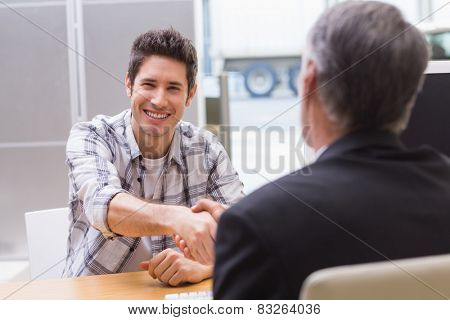 Smiling customer shaking a salesman hand at new car showroom