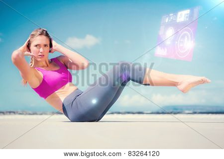 Focused fit blonde doing yoga on the beach against fitness interface