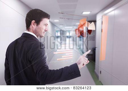 Serious businessman standing and pointing the finger against college hallway