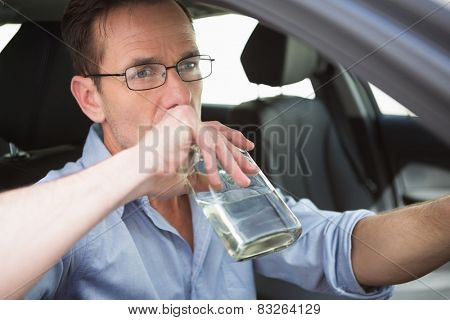 Man drinking wine while driving in his car