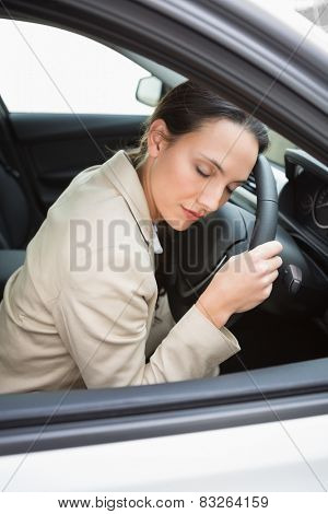 Businesswoman sleeping on the wheel in her car