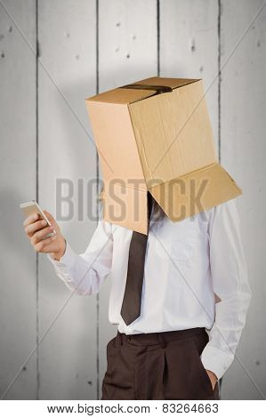 Anonymous businessman with his smartphone against white wood