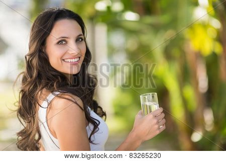 Pretty brunette drinking glass of water on a sunny day