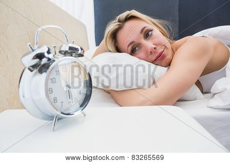 Beautiful blonde in bed with alarm clock on bedside table